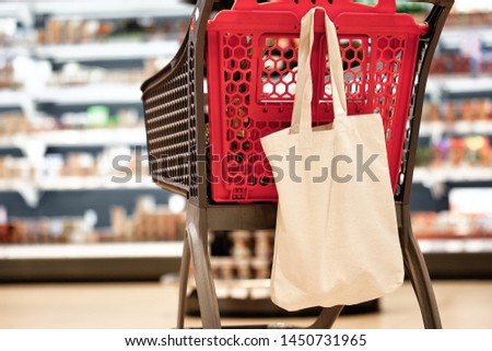 Shopping Plastic Pushcart with White Fabric Bag Isolated on Blurred Grocery Supermarket Shelves Background. Self-service Store Trolley Cart Equipment for Carrying Vegetable and Fruit Food Product