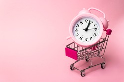 Shopping, purchases, supermarket, sale, mall concept. A metal supermarket trolley in miniature with alarm clock inside. Grocery supermarket, food and eats online buying and delivery concept