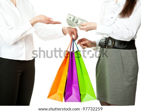Shopping/purchasing/buying concept: young woman buying something in paper bags and paying money to the seller; isolated on white
