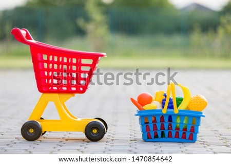 Shopping pushcart and a basket with toy fruits and vegetables. Bright plastic colorful toys for children outdoors on sunny summer day.