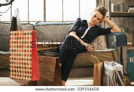 Shopping relieving stress? Tired frustrated brunette woman in elegant clothing sitting on couch among shopping bags in loft apartment.