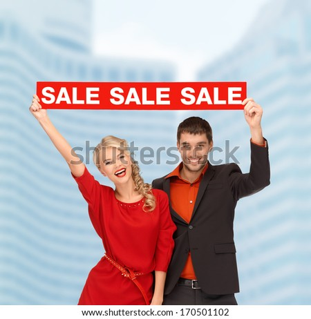 shopping, sale,christmas, couple and x-mas concept - smiling woman and man with red sale sign outdoors