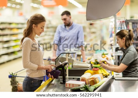 shopping, sale, consumerism, cashless payments and people concept - happy woman buying food at grocery store or supermarket cash register