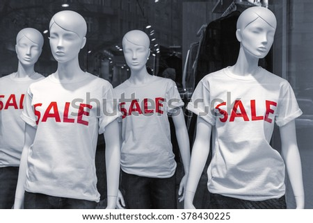 Shopping sale window display with four mannequins wearing t-shirts with text Sale