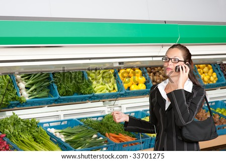 Shopping series - Business woman with mobile phone in a supermarket