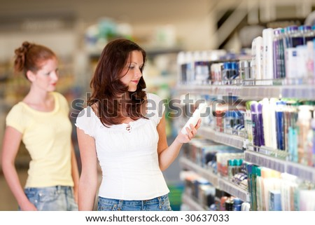Shopping series - Woman holding bottle of shampoo in cosmetics department - stock photo