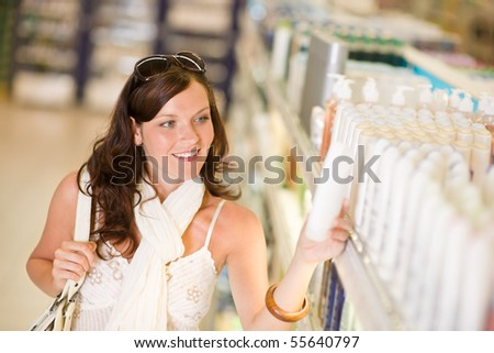 Shopping - smiling woman looking at bottle of shampoo in supermarket