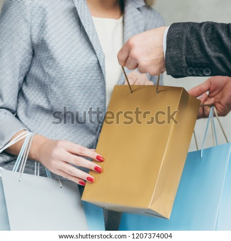 shopping surprise. couple leisure. man show present hidden inside bag. woman looking inside curiously.