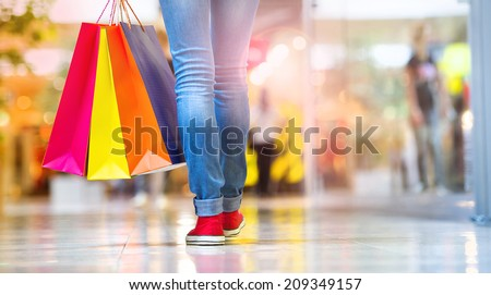 Shopping time, closeup of teenage girl legs with shopping bags at shopping mall