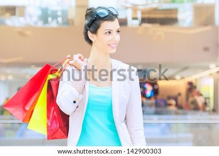 Shopping time Young woman with shopping bags at mall, looking away