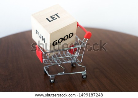Shopping trolley basket or cart with dice with the words are LET, FUN,GOOD  in pushcart.Choose to bring happiness to the life.