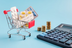 shopping trolley cart filled pills and tablets, calculator and stacks of coins on blue background. most expensive drugs or rising drug prices concept, copy space