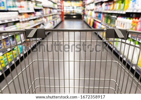 Shopping trolley cart moving in supermarket with motion blur aisle with grocery background 商業照片 ©