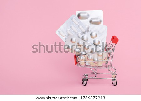 shopping trolley pills, antibiotic isolated on pink. delivery service online order pharmacy. female painkiller tablets, menstruation, contraception, climax, pregnancy, progesterone, pms, medication