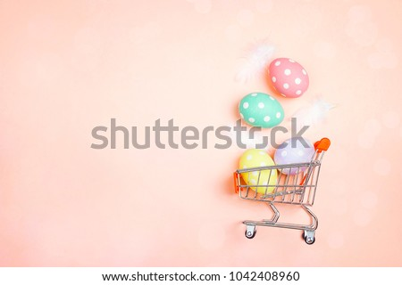 Shopping trolley with Easter eggs and copy space on pink background. Easter shopping and sale.