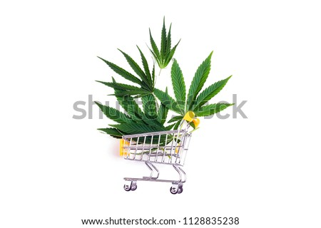 Shopping trolley with fresh cannabis leaf on white background. Flat lay, top view.