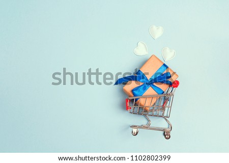 Shopping trolley with gift box, love hearts  and copy space on blue background. Father's Day shopping and sale.