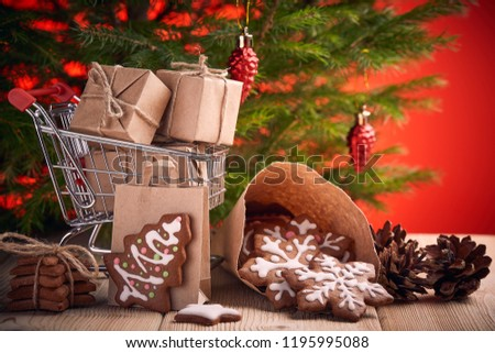 Shopping trolley with gift boxes and gingerbread cookies standing on a wooden table on a red background with Christmas fir tree. Christmas and New Year sale.
