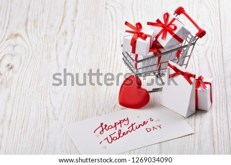 Shopping trolley with gift boxes, red heart and greeting card  on a light wooden  background with copy space. Valentine's day,