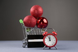 Shopping trolley with red christmas ball and a credit card, red alarm clock next to it.