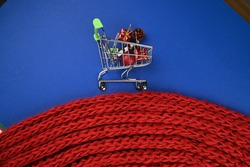Shopping trolley with red christmas decorations on blue background. Christmas discounts concept.