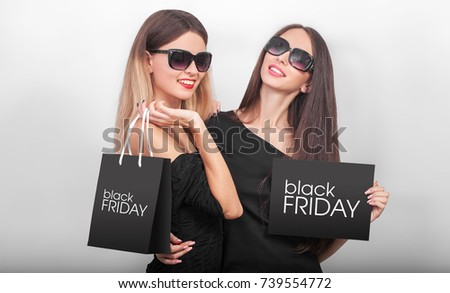 Shopping. Two women holding black bags  on light background in black friday holiday #739554772