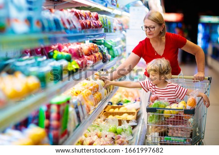 Shopping with kids. Mother and child buying fruit in supermarket. Mom and little boy buy fresh mango in grocery store. Family in shop. Parent and children in a mall choosing vegetables. Healthy food.