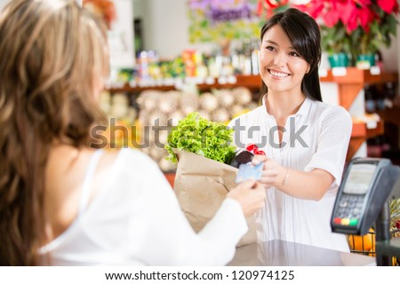 Shopping woman at the checkout paying by card - stock photo
