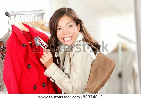 woman excited showing price tag at clothes sale in clothing store
