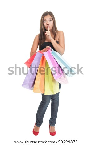 Shopping woman. Full length attractive shopping girl  holding shopping bags saying hush. Isolated on white background.