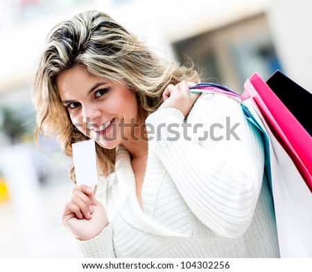 Shopping woman holding a credit or debit card and bags