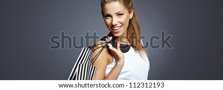 Shopping woman holding bags, isolated on gray studio background.