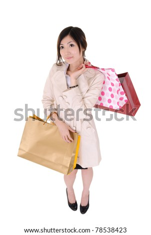 Shopping woman holding colorful bags, high angle shot full length portrait isolated on white background.