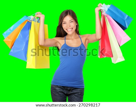 Shopping woman holding shopping bags above her head smiling happy during sale shopping spree. Beautiful young female shopper isolated on green background. stock photo