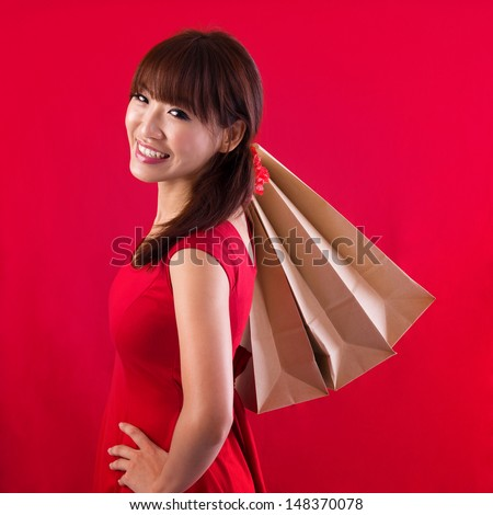 Shopping woman holding shopping bags looking at camera on red background. Beautiful young Asian shopper smiling happy.
