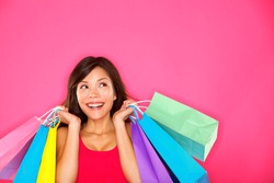 Shopping woman holding shopping bags looking up to the side on pink background at copy space. Beautiful young mixed race Caucasian / Chinese Asian shopper smiling happy.