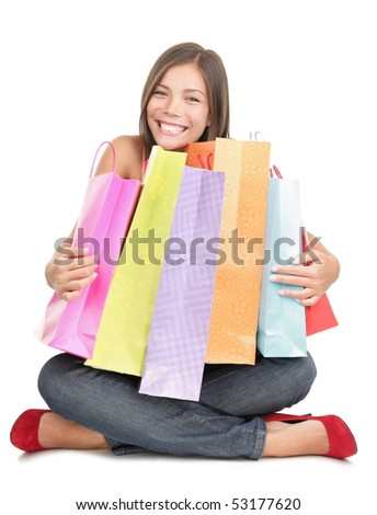 Shopping woman holding shopping bags sitting on the floor being very happy after the sale. Beautiful cute looking mixed Chinese Asian / Caucasian young woman model isolated on white background.