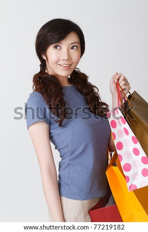 Shopping woman of Asian holding bags, half length closeup portrait on grey studio background.