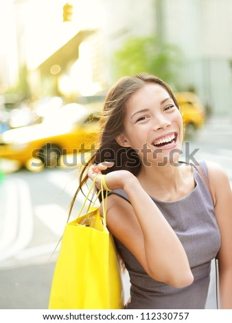 Shopping woman on Manhattan, New York City smiling happy excited walking holding shopping bags with yellow taxi cab in background. Beautiful young multi-racial female shopper laughing joyful outside.