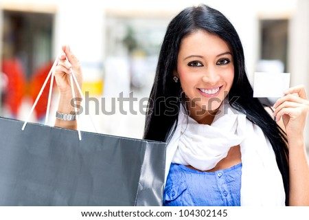 Shopping woman paying by card and holding bags
