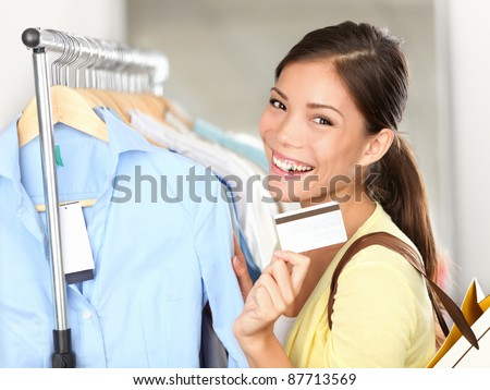 Shopping woman showing credit card or gift card by clothes rack. Happy smiling mixed race Caucasian / Asian female shopping in store.
