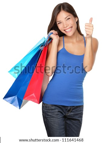 Shopping woman showing thumbs up success holding shopping bags isolated on white background. Beautiful young mixed race Asian Caucasian female shopper.