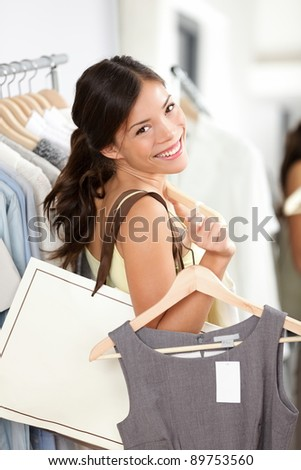 Shopping woman smiling happy holding shopping bag and clothes inside in clothing retail store. Beautiful brunette female model indoors.