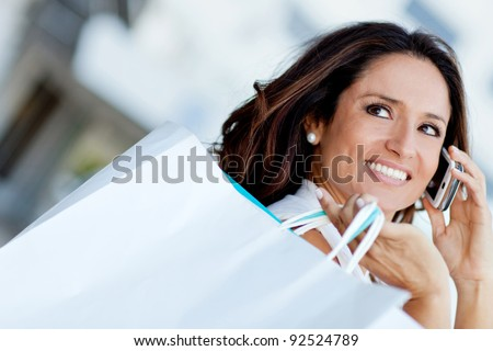 Shopping woman talking on the phone and holding bags - stock photo