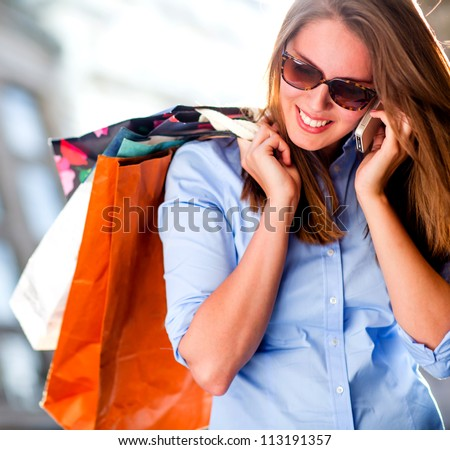 Shopping woman talking on the phone looking happy