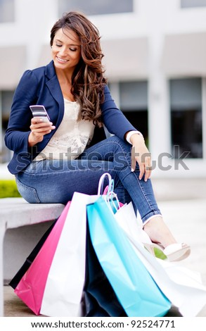 Shopping woman texting on her mobile phone with bags - outdoors