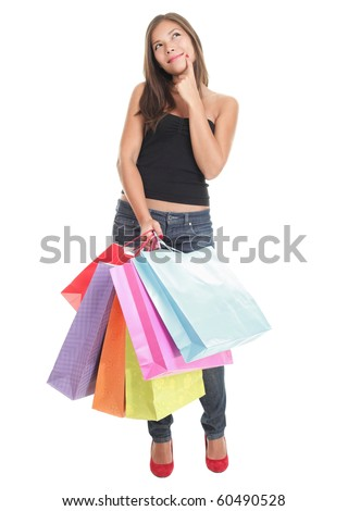 Shopping woman thinking looking up. Young smiling female shopper standing in full length on white background. Mixed Chinese Asian / Caucasian model.
