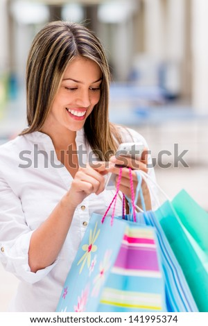 Shopping woman using smart phone at the mall