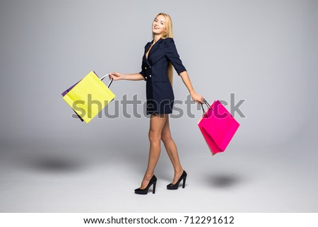 Shopping woman walking and holding bags over grey