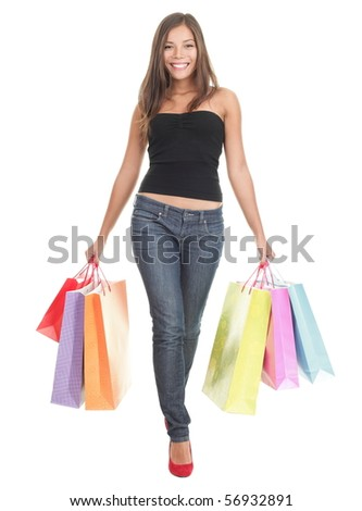 Shopping woman walking holding shopping bags - isolated in full length on white background. Beautiful multiracial Chinese Asian / Caucasian young woman model in her 20s. - stock photo